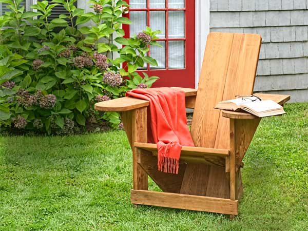 westport chair sitting with an open book and towel draped over it's arms, sitting on a green lawn in front of the red door of a grey cottage