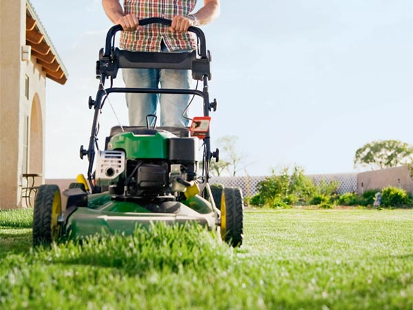 close-up from below of an approaching lawn mower being pushed across a lawn