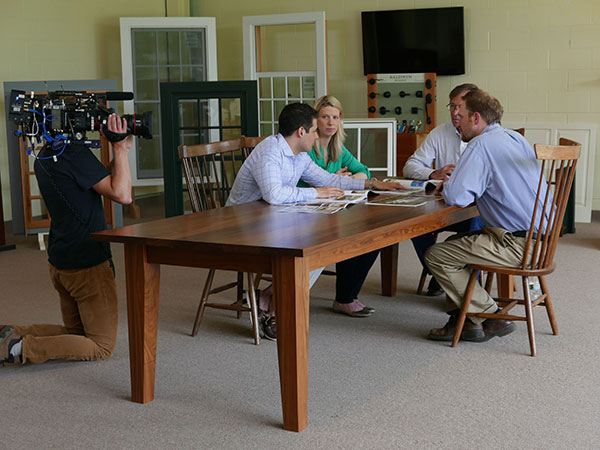 four adults sit around a wood table in the center of a large room. many colorful pages are open on the table,and different styles windows lean against the walls in the background. a person points a video camera at the four sitting