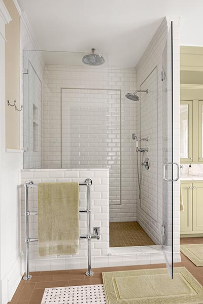 white subway tile wraps the inside and outside of this glass and chrome shower stall with overhead lighting and wall-mounted shower head. brown, white and black tiles patterns the floor, and green throw rugs match the cabinets