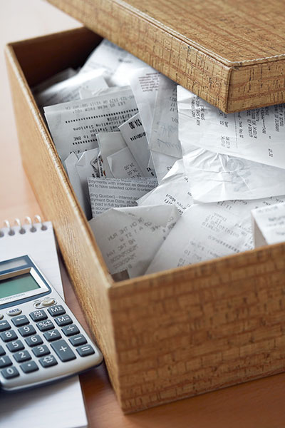 box of receipts next to calculator