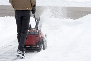 man pushing a snowblower