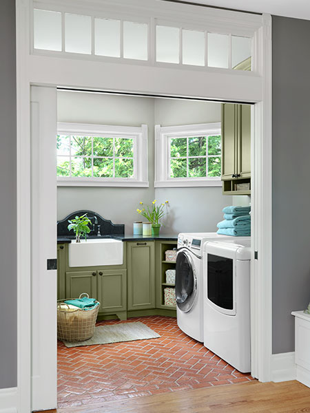 looking through new pocket doors at a newly reorganized and remodeled, clean, modern laundry room with three windows wrapping around the far wall, and green cabinets under the window.