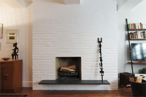 a wood burning, brick fireplace upgraded with clean white paint and a black shelf at the base. An African sculpture stands on the shelf leaning against the brick. other living room items are in the room