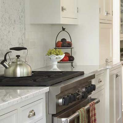 painted cabinets and beefy hardware in this remodeled shingle-style cottage