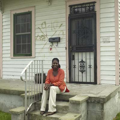 homeowner Rashida sitting on the steps of New Orleans house