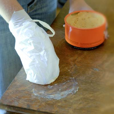 hand wrapped in plastic bag applying wax to a table surface