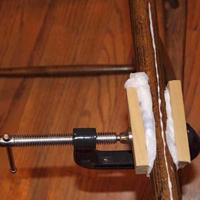 plastic bags wedged between dowel being glued and scrap wood used as clamping blocks