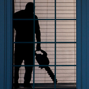 spooky window silhouettes for Halloween of man with chain saw
