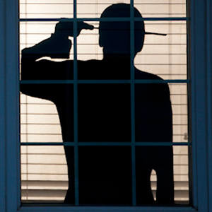 spooky window silhouettes for Halloween of man drilling through his head