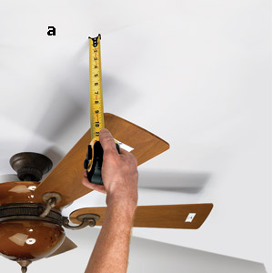 man measuring to balance a ceiling fan