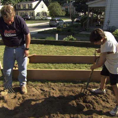 Roger Cook and young boy use pitchforks to turn the soil under the raised garden bed area