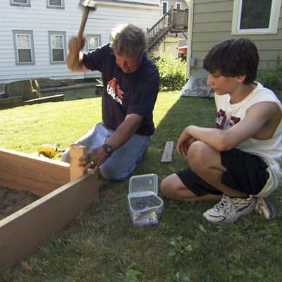 Roger Cook drives stakes in to reinforce the raised garden bed frame