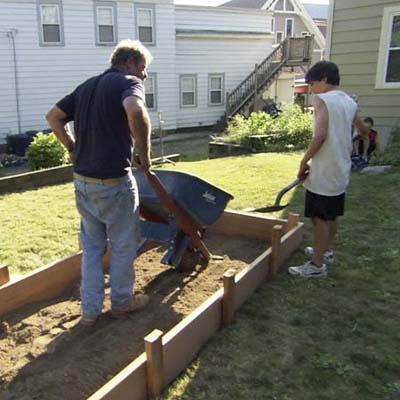 Roger Cook fills the raised garden bed frame with fresh soil using a wheelbarrow