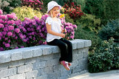 Little girl with flowers on sitting wall