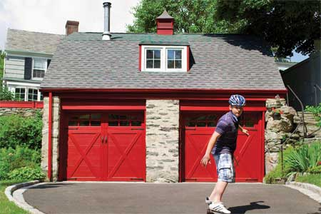 skateboarder rolling downhill from a garage with two red, carriage-style doors