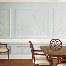 an interior wall patterned with hand-painted branches and leaves