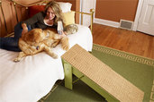 woman lying with her dog on a couch with a completed pet ramp pulled up against it