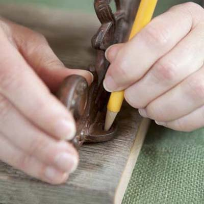 pencil marking the position where the bracket fasteners will go for this vintage porcelain tap towel rack
