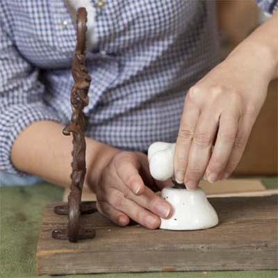 hands attaching a tap to the base mounted on a board to make a vintage porcelain tap towel rack