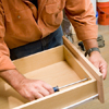 Tom Silva attaching knobs to the drawer fronts of the joined cabinets