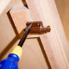 Tom Silva mounting door latches to the inside of the cabinet doors