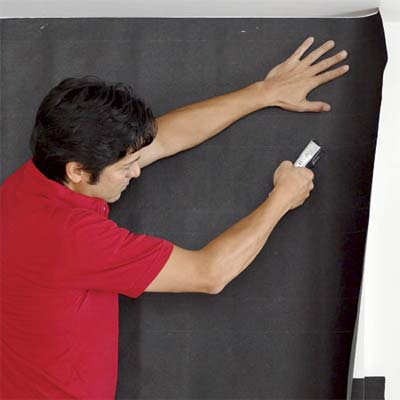 man attaching builder's felt to the front and sides of a fireplace