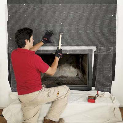 man securing metal lath over the felt of a fireplace to create a stone veneer surround