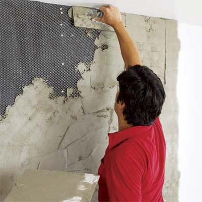 man covering the lath of a fireplace with motar to create a stone veneer surround
