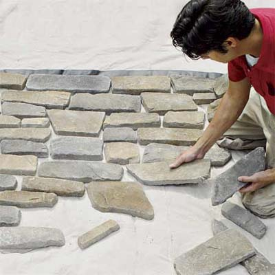 man laying out the stones he'll use to create a stone veneer surround
