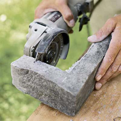hand scoring the corner pieces of stone used to create a stone veneer surround