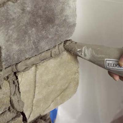 the tip of a grout bag applying grout to the stone when creating a stone veneer fireplace surround
