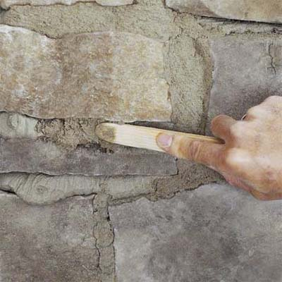 a hand using a striking tool to carve the grout when creating a stone veneer fireplace surround