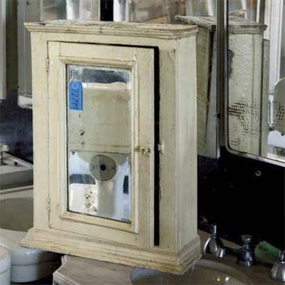 old medicine cabinet standing in front of hanging mirrors in what looks like a salvage shop