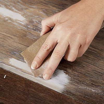 hand sanding down dry wood putty on a cabinet door