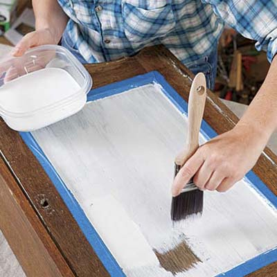 hand brushing latex primer on a cabinet door