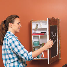 woman putting an envelope in the pocket of a message center made from a vintage medicine cabinet