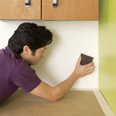 man preparing the wall to install a glass mosaic backsplash