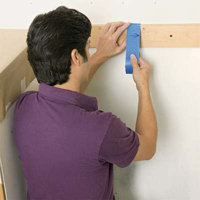 man marking a center line on the wall while preparing to install a glass mosaic backsplash
