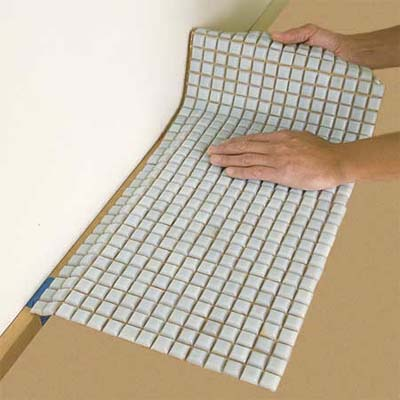 man laying out the tile sheets while preparing to install a glass mosaic backsplash