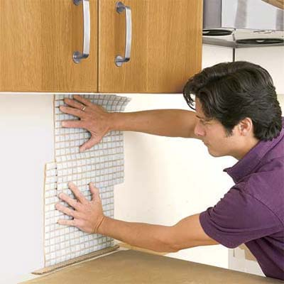 man laying out the remaining tile sheets while preparing to install a glass mosaic backsplash