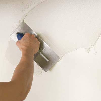 man coating a wall with thinset while preparing to install a glass mosaic backsplash