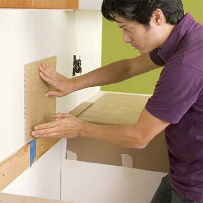 man placing the first tile sheet to install a glass mosaic backsplash