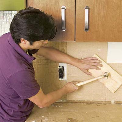 man setting a consistent depth for the tile sheets of a glass mosaic backsplash