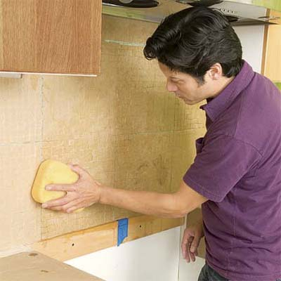 man applying water from a sponge to the paper-covered tile sheets of a glass mosaic backsplash