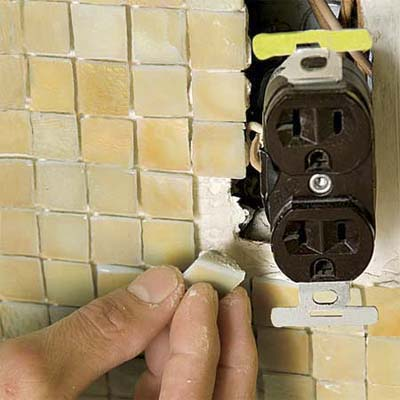 man installing individual tiles to fit around obstructions in a glass mosaic backsplash