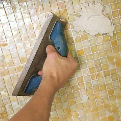 man grouting the joints of the installed glass mosaic backsplash