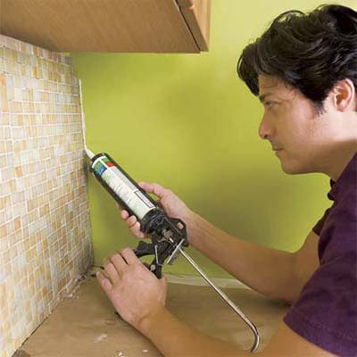 man caulking the perimeter of the installed glass mosaic backsplash