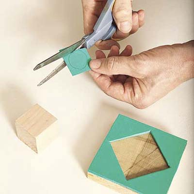 cutting patterns out of craft foam to glue onto scrap wood blocks