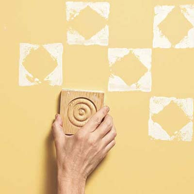 using a stamp on a yellow-painted wall